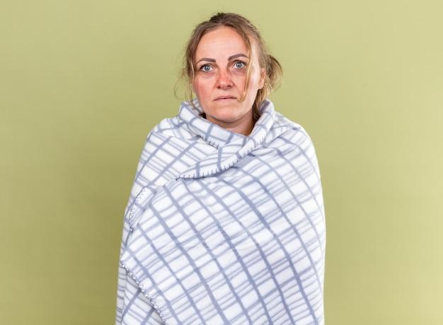 독감과 감기로 고통받는 끔찍한 느낌의 담요에 싸인 건강에 해로운 여자