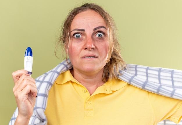 독감과 감기로 고통받는 담요에 싸여 건강에 해로운 여자는 온도계를 들고 발열이 녹색 벽 위에 서 무서워