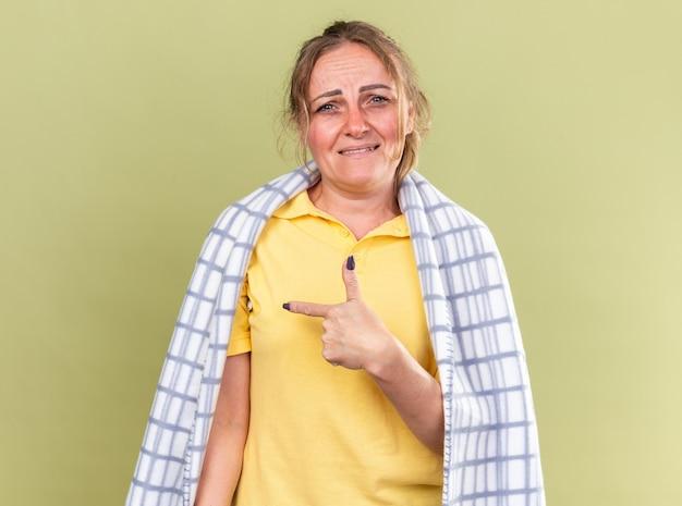 독감과 감기로 고통받는 담요에 싸여 건강에 해로운 여자는 녹색 벽 위에 서있는 옆으로 검지 손가락으로 가리키는 열이 있습니다.