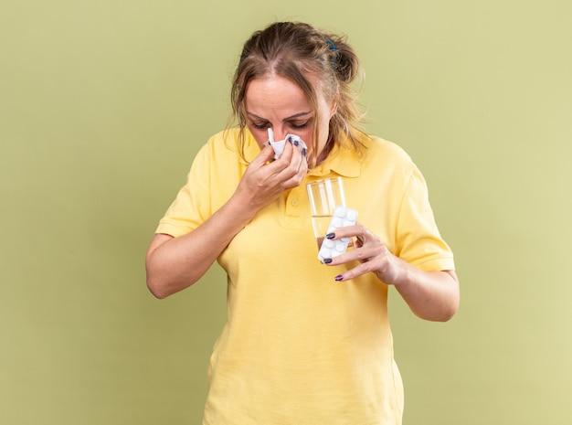 Donna malsana in camicia gialla che si sente terribile con in mano un bicchiere d'acqua e pillole che soffia il naso che cola starnuti nei tessuti affetti da influenza in piedi sul muro verde