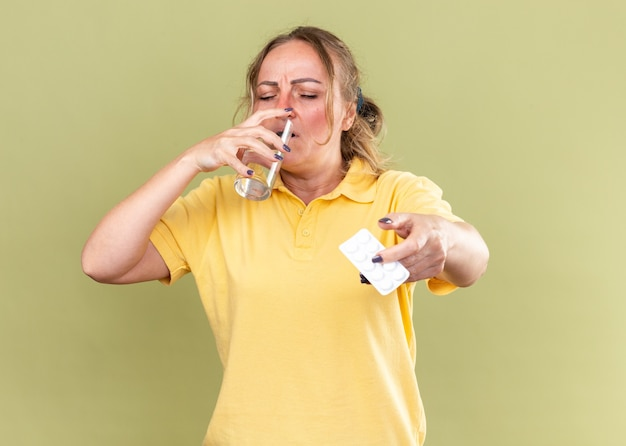 Donna malsana in camicia gialla che si sente terribile con in mano un bicchiere d'acqua e pillole che beve acqua che soffre di influenza e raffreddore in piedi sul muro verde