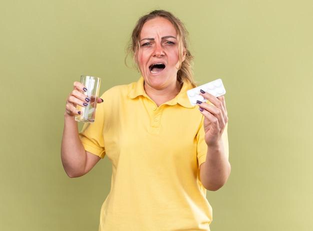 Donna malsana in camicia gialla che si sente terribile con in mano un bicchiere d'acqua e pillole che soffre di influenza e raffreddore in piedi sul muro verde