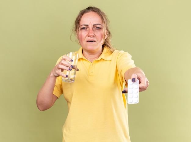 Donna malsana in camicia gialla che si sente malissimo tenendo in mano un bicchiere d'acqua e pillole che soffre di influenza