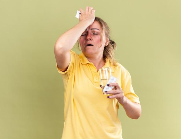 一个不健康的女人穿着黄色衬衫,感觉很糟糕,拿着一杯水和药片,触摸她的前额,因为感冒鼻子阻塞而遭受强烈的头痛
