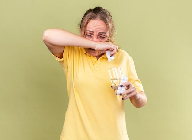 Donna malsana in camicia gialla che si sente terribile con in mano un bicchiere d'acqua e pillole che si asciugano il naso che cola soffre di influenza in piedi sul muro verde