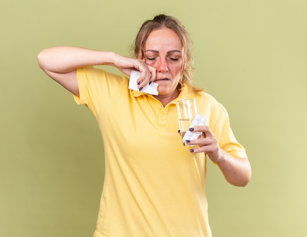 Donna malsana in camicia gialla che si sente terribile con in mano un bicchiere d'acqua e pillole che si asciugano il naso che cola soffre di influenza suffering