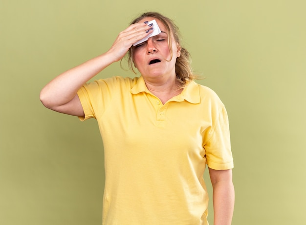 Unhealthy woman in yellow shirt feeling terrible wiping her forehead with tissue having flu and fever