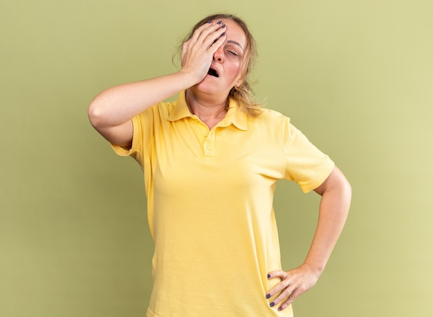 Donna malsana in camicia gialla che si sente male a toccarsi la fronte mentre ha le vertigini con l'influenza in piedi sul muro verde