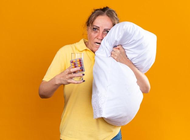 Donna malsana in camicia gialla che soffre di influenza e raffreddore sensazione di malessere abbracciando cuscino con pillole e bicchiere d'acqua in piedi sul muro arancione