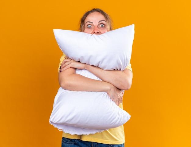 Donna malsana in camicia gialla che soffre di influenza e freddo si sente male abbracciando un cuscino spaventata in piedi sul muro arancione over