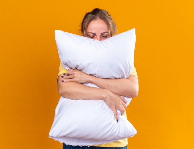 Unhealthy woman in yellow shirt suffering from flu and cold feeling unwell hugging pillow wants to sleep standing over orange wall