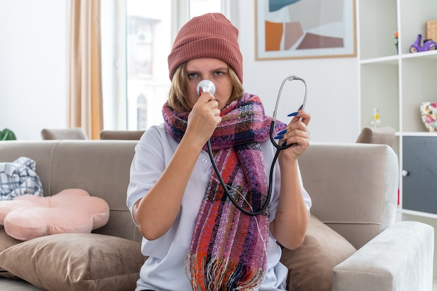 Unhealthy young woman in hat with warm scarf around neck feeling terrible suffering from virus holding stethoscope sitting on couch in light living room