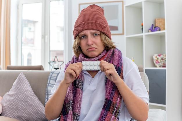 Giovane donna malsana in cappello con sciarpa calda intorno al collo sentirsi male e malata che soffre di raffreddore e influenza con in mano pillole che sembra preoccupata seduta sul divano in un soggiorno luminoso