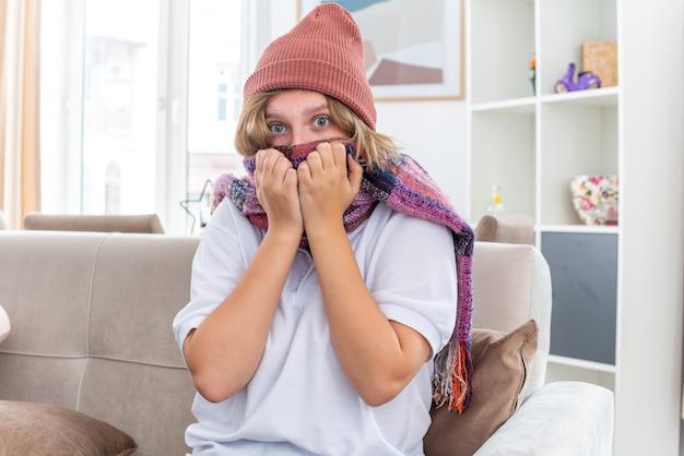 Giovane donna malsana in cappello con sciarpa calda intorno al collo sensazione di malessere e malata che soffre di raffreddore e influenza che sembra preoccupata seduta sul divano in un soggiorno luminoso