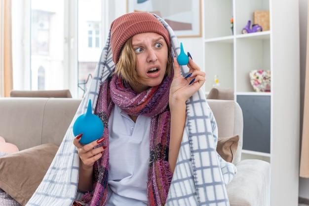 Malsana giovane donna in cappello avvolto in una coperta sensazione di malessere e malati holding clisteri guardando confuso avendo dubbi seduto sul divano nella luce del soggiorno