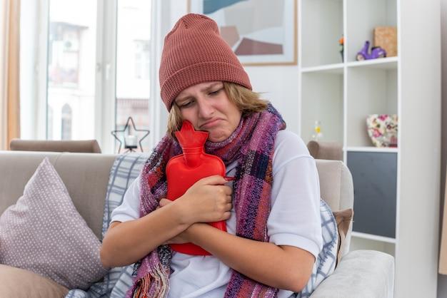 목 주위에 따뜻한 스카프가 달린 모자에 건강에 해로운 젊은 여성이 가벼운 거실에서 소파에 앉아 걱정되는 감기와 독감으로 고통받는 감기와 독감으로 고통받습니다.