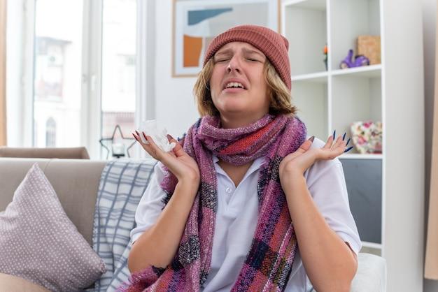 목 주위에 따뜻한 스카프가 달린 모자에 건강에 해로운 젊은 여성이 감기와 독감으로 고통 받고 아픈 느낌이 들며 가벼운 거실에서 소파에 앉아 팔을 제기하여 걱정하고 실망했습니다.