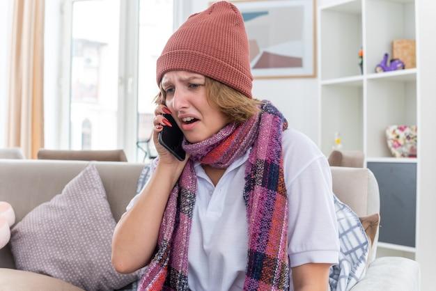 明るいリビングルームのソファに座って携帯電話で話している間、首に暖かいスカーフを巻いた帽子をかぶった不健康な若い女性が、風邪やインフルエンザに苦しんでいる