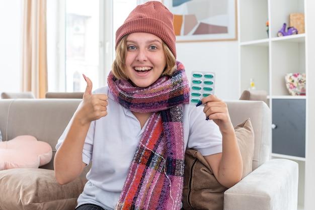 風邪やインフルエンザに苦しんでいる首の周りに暖かいスカーフを持った帽子をかぶった不健康な若い女性