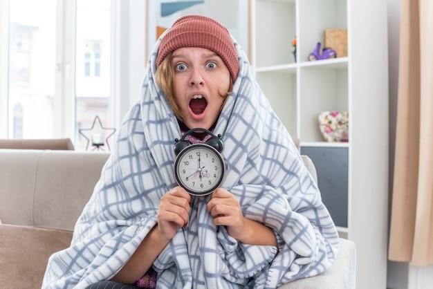 Нездоровая молодая женщина в шляпе, завернутой в одеяло, чувствует себя нездоровой и больной, держит будильник, выглядит удивленной, страдает от простуды и гриппа, сидя на диване в светлой гостиной