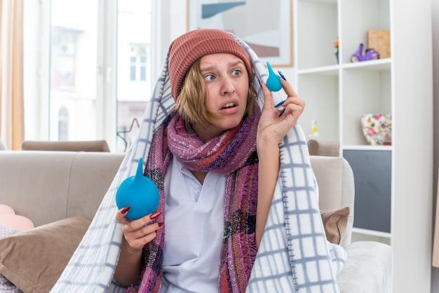 Нездоровая молодая женщина в шляпе, завернутой в одеяло, чувствует себя нездоровой и больной, держит клизмы, выглядит смущенной и сомневается, сидя на диване в светлой гостиной