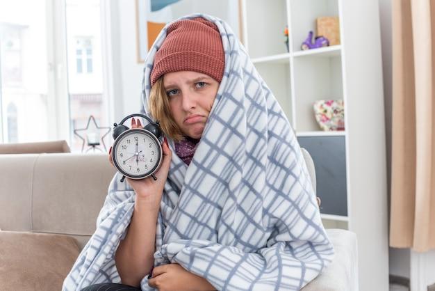 Нездоровая молодая женщина в шляпе, завернутая в одеяло, держит будильник, чувствует себя нездоровой и больной, страдает от простуды и гриппа, смотрит с грустным выражением лица, сидя на диване в светлой гостиной