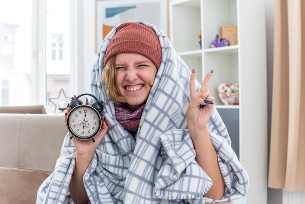 Нездоровая молодая женщина в шляпе, завернутая в одеяло, держит будильник, улыбаясь, показывая v-знак, чувствуя себя лучше, сидя на диване в светлой гостиной