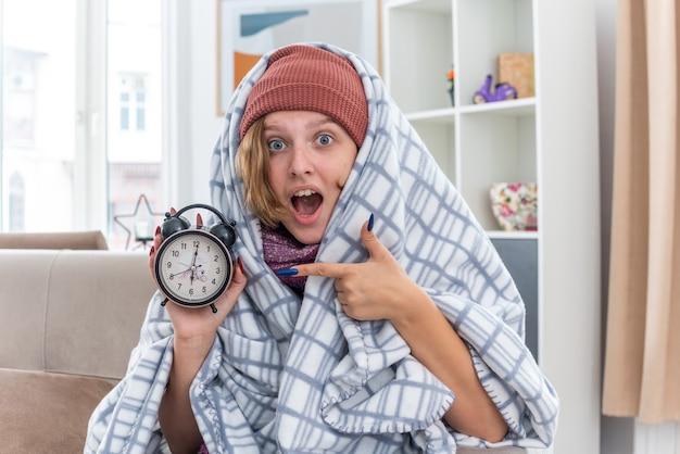 Нездоровая молодая женщина в шляпе, завернутая в одеяло, держит будильник с удивлением, сидя на диване в светлой гостиной