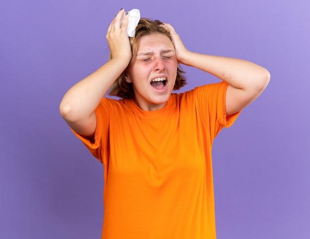 열과 강한 두통으로 고통받는 그녀의 머리를 만지고 끔찍한 소리를 지르는 주황색 티셔츠에 건강에 해로운 젊은 여성