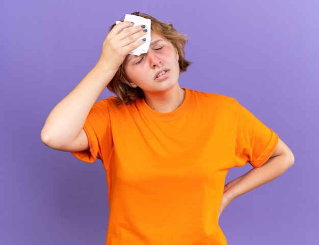 주황색 티셔츠에 건강에 해로운 젊은 여성이 보라색 벽 위에 서있는 강한 두통으로 고통받는 현기증을 느끼면서 그녀의 머리를 만지는 끔찍한 느낌