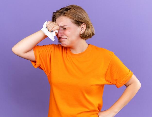주황색 티셔츠에 건강에 해로운 젊은 여성이 바이러스로 고통받는 열과 두통이있는 그녀의 이마를 만지는 조직으로 끔찍한 느낌