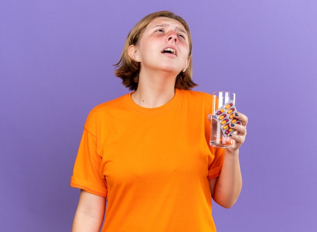 オレンジ色のtシャツを着た不健康な若い女性がインフルエンザのくしゃみに苦しんでいる水と錠剤のガラスを保持して気分が悪い