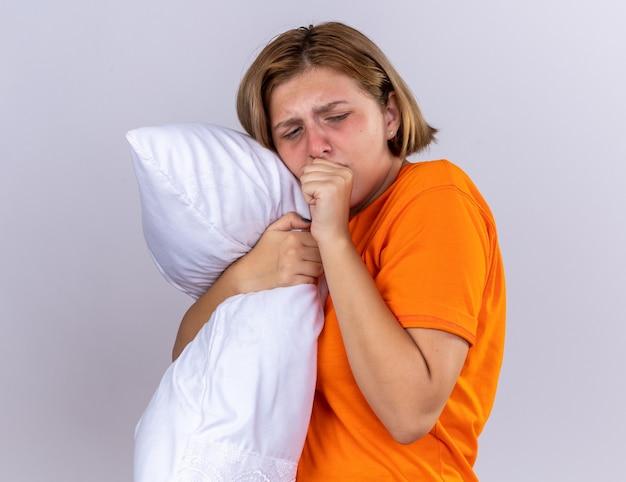 흰 벽 위에 서있는 주먹에 독감 기침으로 아픈 고통을 느끼는 베개를 들고 오렌지 티셔츠에 건강에 해로운 젊은 여자