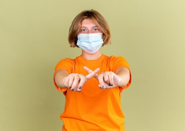 顔の保護マスクを着たオレンジ色のtシャツを着た不健康な若い女性は、ウイルスに苦しんでいると感じ、緑の壁の上に立つ人差し指を横切るジェスチャーを止める