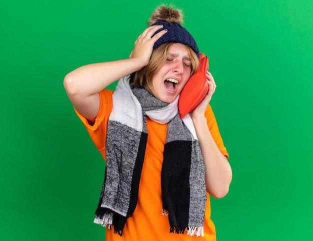 オレンジ色のtシャツを着た不健康な若い女性が帽子と暖かいスカーフを首に巻いて、風邪やインフルエンザに悩まされている湯たんぽを持ってひどい気分になっている