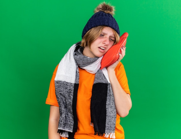 オレンジ色の t シャツを着た不健康な若い女性で、帽子と暖かいスカーフを首にかけ、緑の壁の上に立って、風邪やインフルエンザに苦しんでいる湯たんぽを持ってひどいと感じた