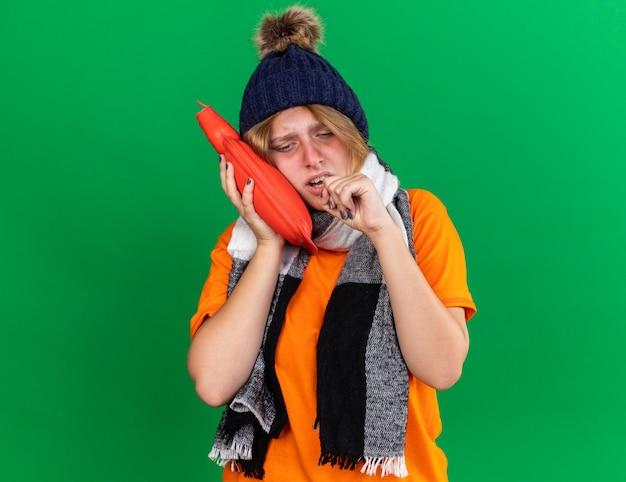 寒さに苦しんでいる湯たんぽを持ってひどい感じ首の周りに帽子と暖かいスカーフとオレンジ色のtシャツの不健康な若い女性