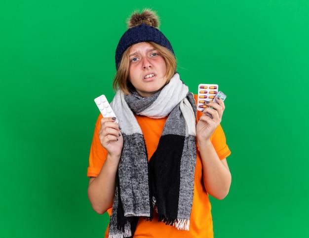帽子と首の周りに暖かいスカーフとオレンジ色のtシャツを着た不健康な若い女性はインフルエンザに苦しんで丸薬を保持してひどい感じ