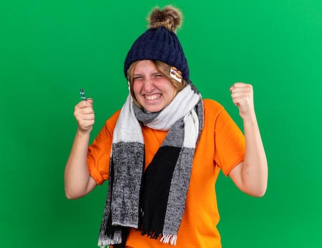 オレンジ色のtシャツを着た不健康な若い女性、帽子と暖かいスカーフを首に巻いて、ウイルスに苦しんでいる丸薬を持ってひどい気分になっている怒っている狂った狂った握りこぶし