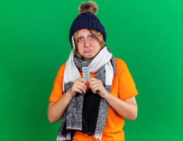 帽子と首の周りに暖かいスカーフとオレンジ色のtシャツを着た不健康な若い女性は、唇をすぼめる悲しげな表情でウイルスに苦しんでいる丸薬を持ってひどい感じ
