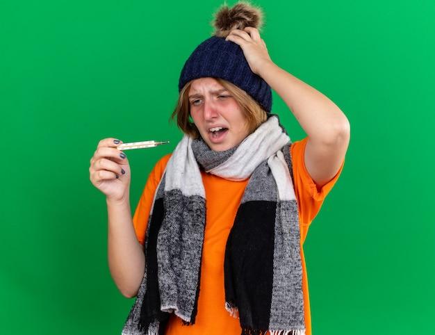 모자와 목 주위에 따뜻한 스카프가있는 주황색 티셔츠에 건강에 해로운 젊은 여성이 끔찍한 느낌의 온도계를 들고 독감으로 고통받는 열이 실망했습니다.