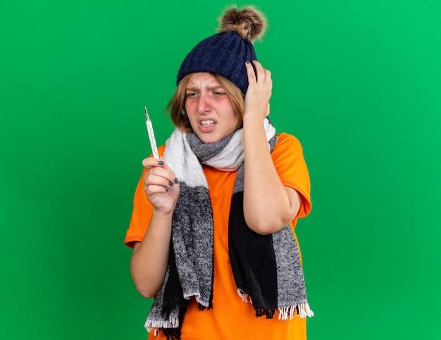독감으로 고통받는 열이있는 끔찍한 지주 온도계 느낌 모자와 따뜻한 스카프가 달린 주황색 티셔츠에 건강에 해로운 젊은 여성