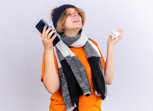 Нездоровая молодая женщина в оранжевой футболке с теплым шарфом на шее и шляпе чувствует себя ужасно, держа смартфон и салфетку, страдающую от простуды и гриппа, разочарованно смотрит на белую стену
