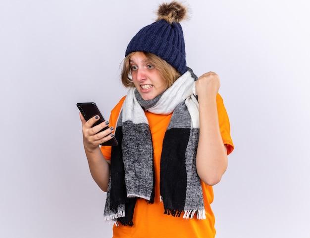 Нездоровая молодая женщина в оранжевой футболке с теплым шарфом на шее и шляпе чувствует себя ужасно, глядя на свой смартфон с агрессивным выражением лица, поднимая кулак
