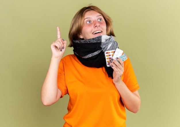 Нездоровая молодая женщина в оранжевой футболке с теплым шарфом на шее чувствует себя лучше, держа разные таблетки, улыбаясь, показывая новую идею, показывая указательный палец