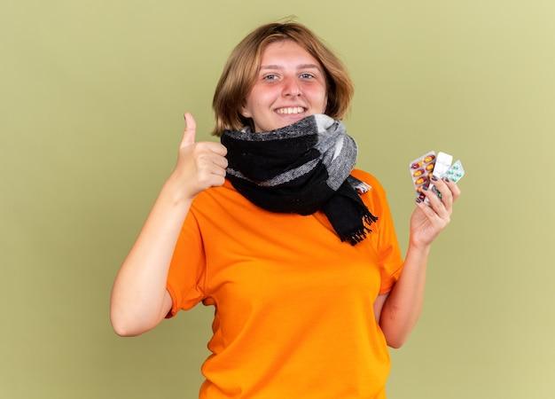 Нездоровая молодая женщина в оранжевой футболке с теплым шарфом на шее чувствует себя лучше, держа разные таблетки, улыбаясь, показывая пальцы вверх, стоя над зеленой стеной
