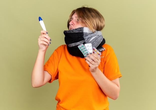 Нездоровая молодая женщина в оранжевой футболке с теплым шарфом на шее чувствует себя ужасно, страдая от гриппа, держит таблетки, проверяя температуру с помощью термометра, выглядит обеспокоенно на зеленой стене