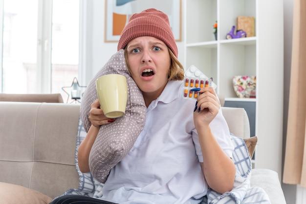 Нездоровая молодая женщина в теплой шляпе с одеялом, чувствуя себя нездоровой и больной, страдающая от простуды и гриппа, держа подушку и чашку с таблетками, обеспокоенная, сидя на диване в светлой гостиной
