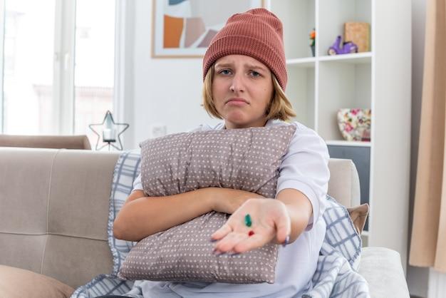 暖かい帽子をかぶった不健康な若い女性で、毛布が気分が悪く、風邪やインフルエンザに苦しんでいると、明るいリビング ルームのソファに座って心配している枕と丸薬を持っている