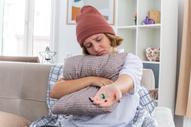 따뜻한 모자에 건강에 해로운 젊은 여성이 감기와 독감 베개와 약을 들고 몸이 불편하고 가벼운 거실에서 소파에 앉아 아픈 느낌